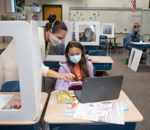 Female teacher and fifth-grade student with masks